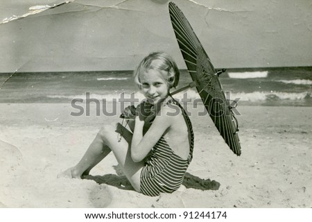 Vintage photo of young girl with umbrella on beach (fifties) - stock photo