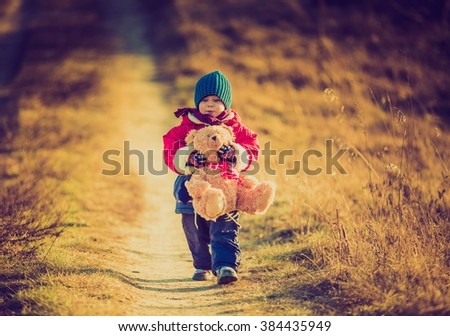 Vintage photo of young happy boy playing outdoor in beautiful rural landscape in golden light at spring. Happy childhood spent in the countryside. - stock photo