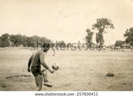 Vintage photo of young man playing football (1960's) - stock photo