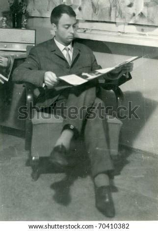 Vintage photo of young man reading (circa 1960) - stock photo