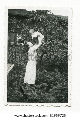 Vintage photo of young mother with baby (early forties) - stock photo