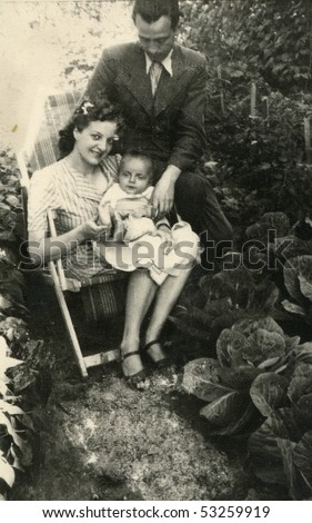 Vintage photo of young parents with their baby (forties) - stock photo