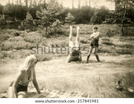 Vintage photo of young people exercising outdoor (1960's) - stock photo