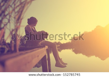 Vintage photo of young woman relaxing with her dog at the lake in sunset - stock photo