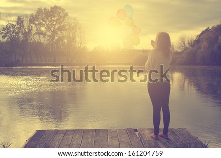 Vintage photo of young woman with balloons - stock photo