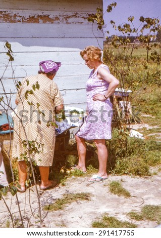 Vintage photo (scanned reversal film) of elderly mother and her daughter on farm, early 1970's - stock photo