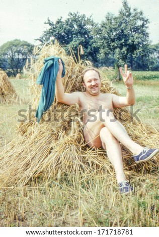 Vintage photo (scanned reversal film) of man resting in bundle of straw (early eighties) - stock photo