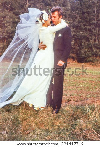 Vintage photo (scanned reversal film) of newlyweds kissing outdoor, early 1970's