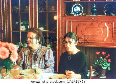 Vintage photo (scanned reversal film) of two women during a family dinner (early eighties) - stock photo