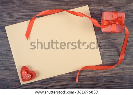 Vintage photo, Wrapped gift with ribbon and love letter in envelope on wooden background, decoration for Valentines Day, copy space for text - stock photo