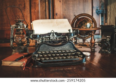 vintage photography still life with typewriter, folding camera, globe map and book on a wood table. - stock photo