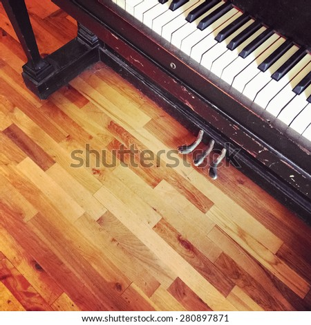 Vintage piano on old wooden floor, view from top. - stock photo