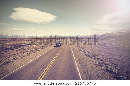 Vintage picture of car on endless country highway, Ruta 40 in Argentina. - stock photo