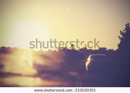 Vintage picture of road with cars in motion against sun. - stock photo