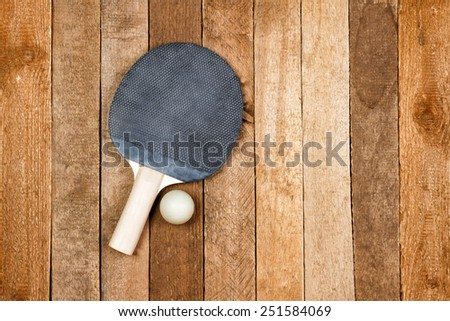 Vintage ping pong paddle on wooden background - stock photo