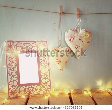 vintage pink classical frame, fabric hearts hanging on the rope and garland lights, on wooden table. retro filtered image - stock photo