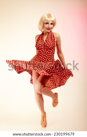 Vintage pinup style. Full length of stylish woman dancing. Girl in blond wig and retro spotted red dress on pink. Disguise. Party. - stock photo