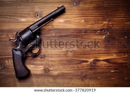Vintage pistols on wooden background - stock photo