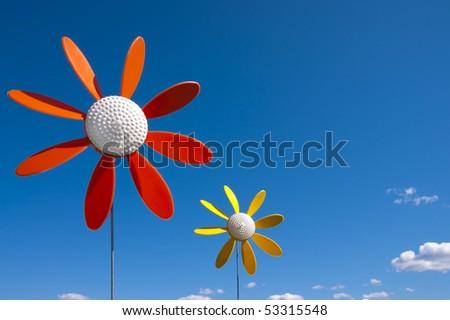 Vintage plastic flowers windmill on a blue sky. - stock photo