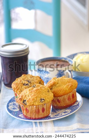 Vintage plate of whole grain (wheat/oat/almond) blueberry muffins with blueberry jam, fresh butter, and cup of hot black tea - stock photo