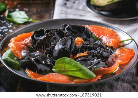 Vintage plate with black homemade ravioli with salted salmon and fresh spinach.