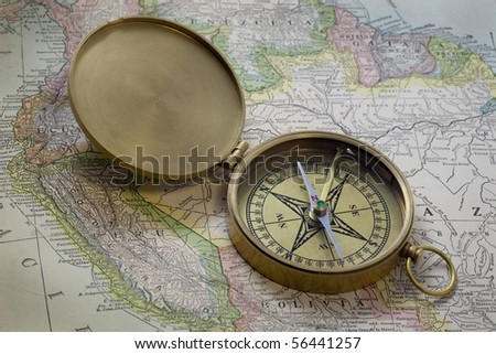 vintage pocket brass compass over old map of South America published in 1926 - expired copyrights) - stock photo