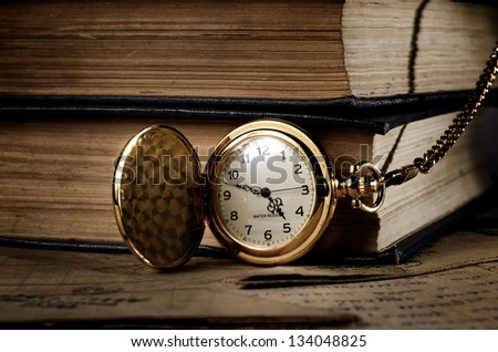 vintage pocket clock and old books - stock photo