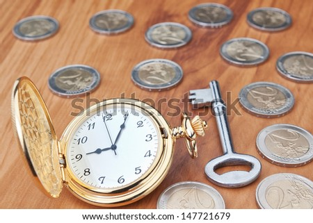 Vintage pocket watch and a key against the euro coins. Close-up. - stock photo