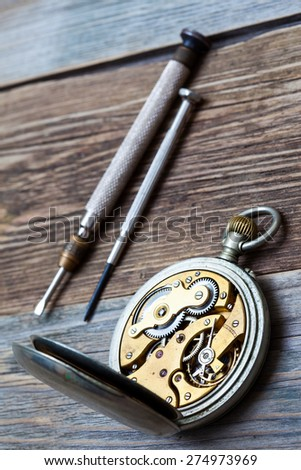 vintage pocket watch and a screwdriver. still life - stock photo