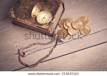 vintage pocket watch and gold coins - stock photo