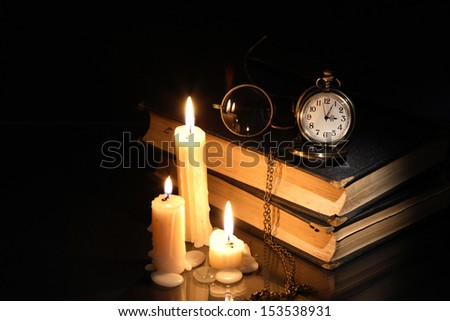 Vintage pocket watch and spectacles on old books near lighting candles - stock photo