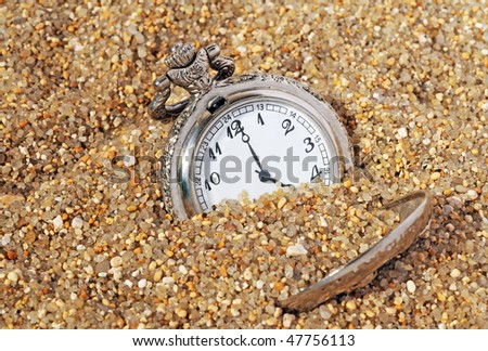 vintage pocket watch in the sand. time concept - stock photo