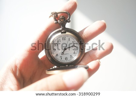 Vintage pocket watch in woman hand with sunlight and shadow. Close up. Toned image.