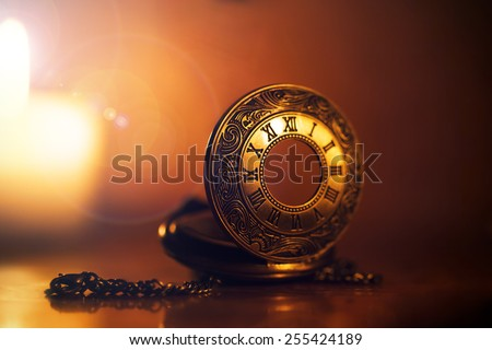 Vintage  pocket watch near few lighting candles on dark background - stock photo