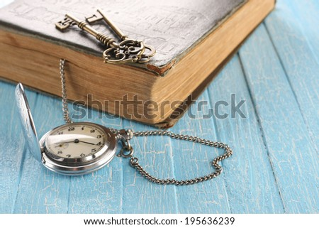 Vintage pocket watch, old book and a brass key on painted blue boards - stock photo
