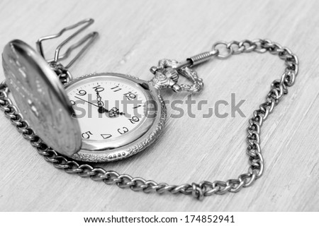 vintage pocket watch on a gold chain on the table