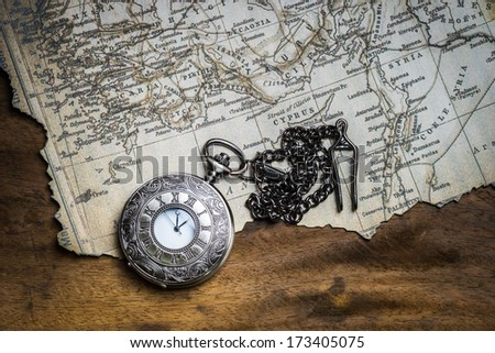 Vintage pocket watch on burnt ancient map - stock photo