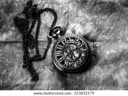 Vintage pocket watch on fabric black and white time concept - stock photo