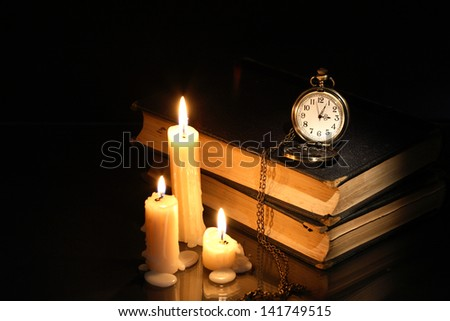 Vintage pocket watch on old books near lighting candles - stock photo