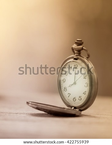 vintage pocket  watch on wooden  table with blur background - stock photo