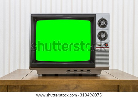 Vintage portable television on old craftsman style table with chroma screen. - stock photo