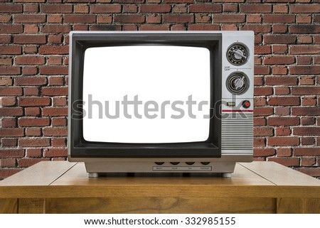 Vintage portable television with red brick wall and cut out screen. - stock photo