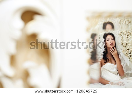 Vintage portrait of a beautiful queen like girl (bride) in the white bedroom. Retro style. Reflection in the mirror. Studio shot