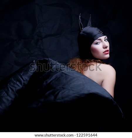 vintage portrait of a glamorous animal red-haired girl over wrinkled black paper background. studio shot