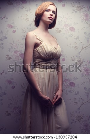 Vintage portrait of a glamorous doll-like retro girl posing in gorgeous classic dress . Hollywood style (film noir). Studio shot