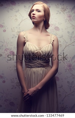 Vintage portrait of a glamorous doll-like retro girl posing in gorgeous classic dress . Hollywood style (film noir). Perfect skin and hairdo. Studio shot - stock photo