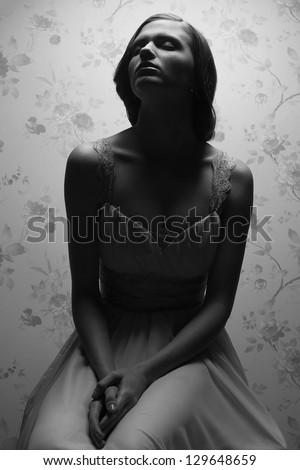 Vintage portrait of a glamorous retro girl posing in gorgeous classic dress. Hollywood style (film noir). Studio shot - stock photo