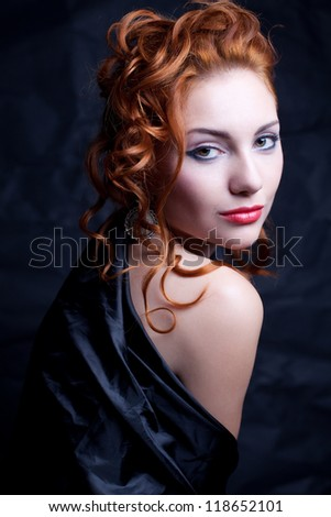 Vintage portrait of a glamourous queen like girl over wrinkled black paper background. Retro style. Studio shot - stock photo