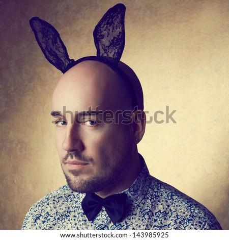 Vintage portrait of a handsome glamorous bald bunny-man posing over golden background. Close up. Copy-space. Studio shot - stock photo