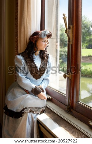 "Vintage portrait of a victorian lady standing by a castle window. Shot in the antique castle ""Den Brandt"" in Antwerp, Belgium (with signed property release for the Castle interiors). - stock photo"